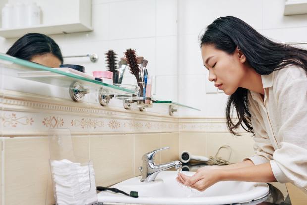 девушка восточной внешности умывается в ванной комнате