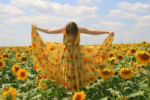 девушка в желтом сарафане стоит в поле с яркими подсолнухами