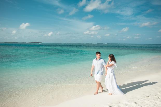 мужчина и женщина в светлых нарядах идут по берегу моря