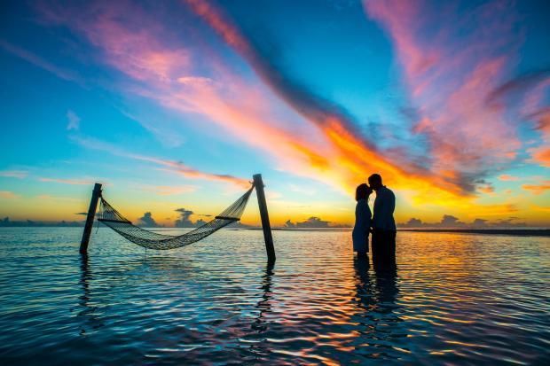 влюбленная пара в море на фоне заката