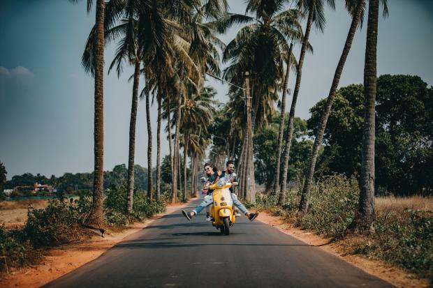 пара на мотоцикле едет под пальмами