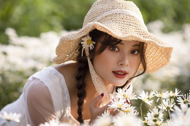 девушка в соломенной шляпке наклонилась к цветам