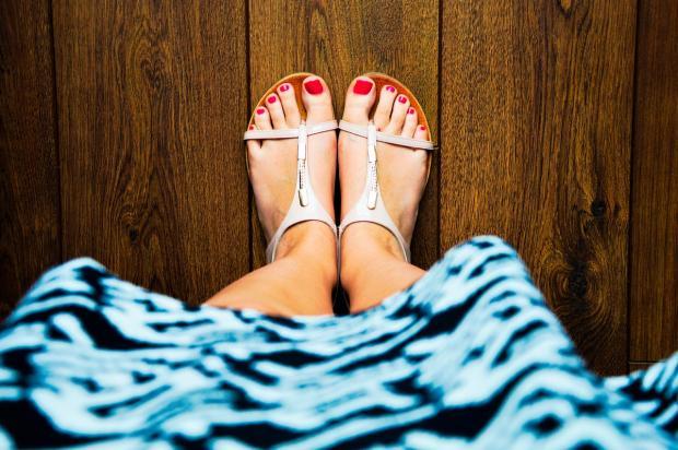 ноги с ярко накрашенными ногтями в босоножках