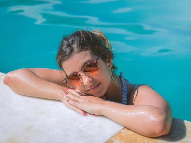 девушка в солнцезащитных очках в бассейне