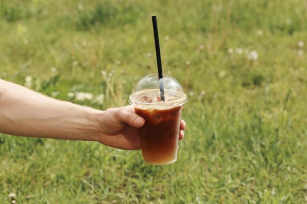 стаканчик с кофе со льдом в руке
