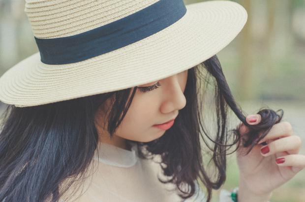 брюнетка в соломенной шляпе держит прядь волос