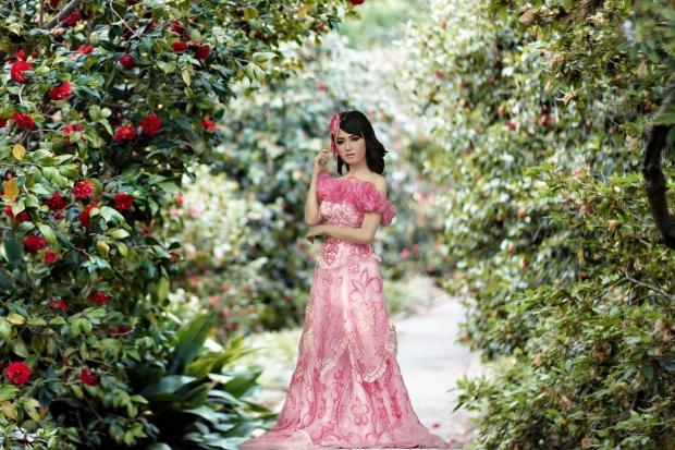красивая девушка в розовом платье стоит в цветущем саду