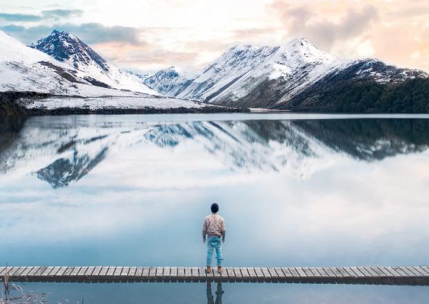 Мужчина стоит на деревянном мосту посреди водоема в горах