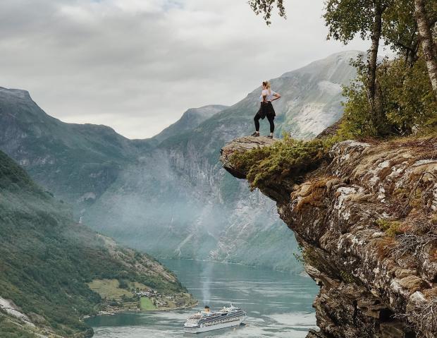 молодая девушка стоит на обрыве и смотрит на горы