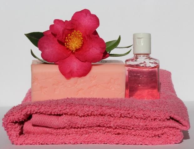 на бордовом полотенце лежит душистое туалетное мыло