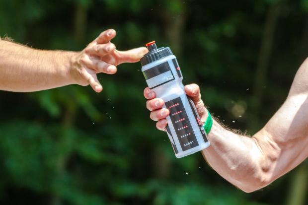 один мужчина передает бутылку воды другому