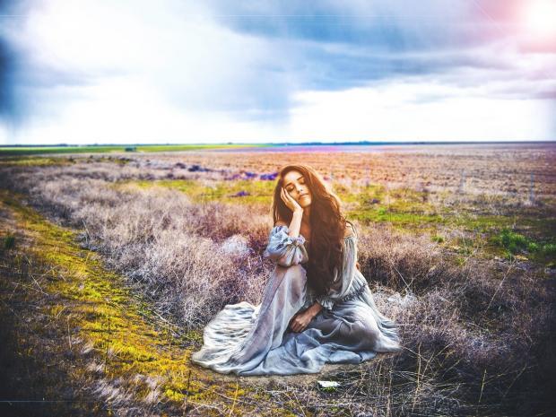 девушка в длинном платье сидит среди цветущего поля
