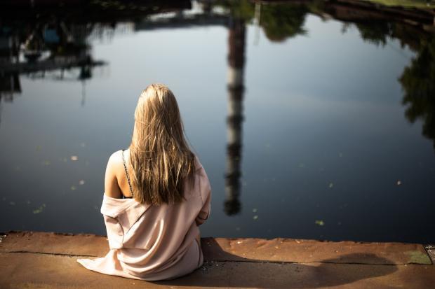 девушка сидит на берегу водоема