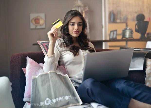 девушка с банковской картой в руке работает на ноутбуке