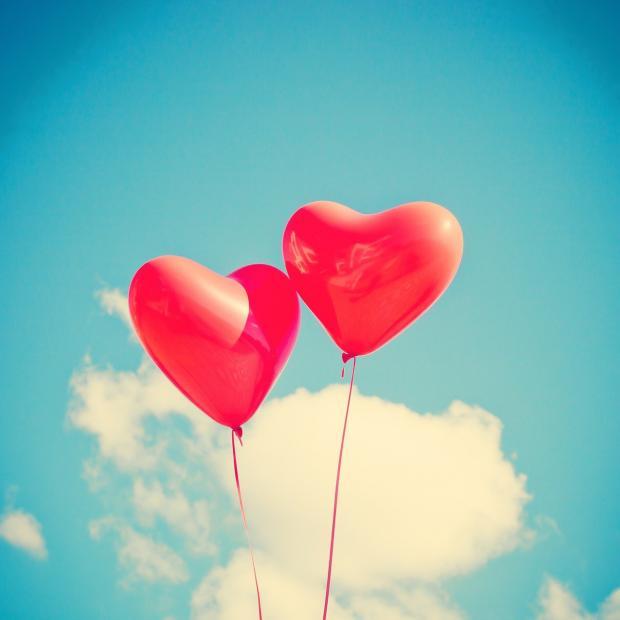 два воздушных шара в виде сердца на фоне голубого неба
