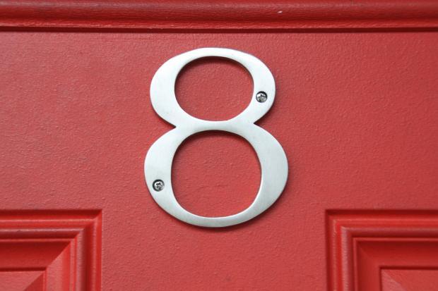 прикреплена цифра восемь на красной двери