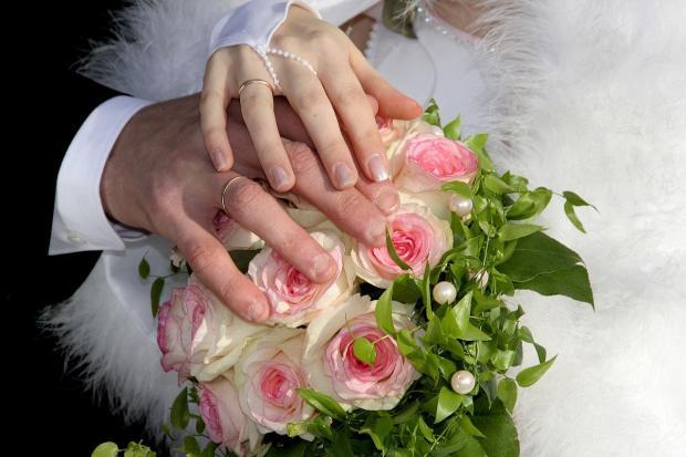 молодожены держат правые руки на букете с цветами