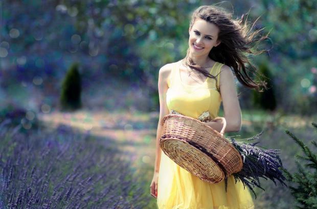 девушка в желтом сарафане смеется и держит в руке плетеную корзинку с лавандой