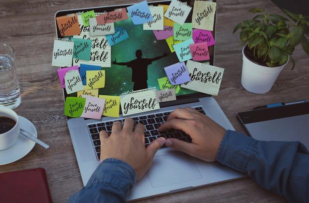 на ноутбук наклеены разноцветные листочки с делами и планами