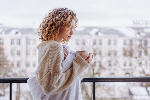 девушка на балконе с чашкой кофе в руках