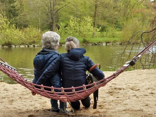 две женщины сидят в гамаке на берегу реки
