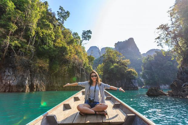 девушка на лодке плывет по горной реке