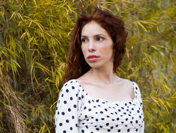 длинноволосая девушка в белой блузе в горошек