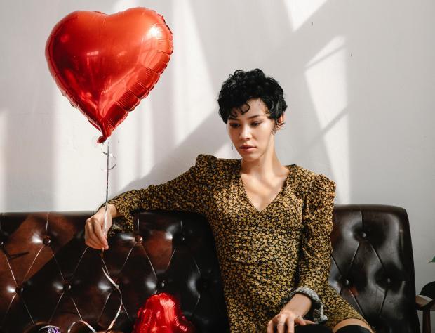 девушка в темном платье сидит на диване и держит воздушный шарик в виде сердца
