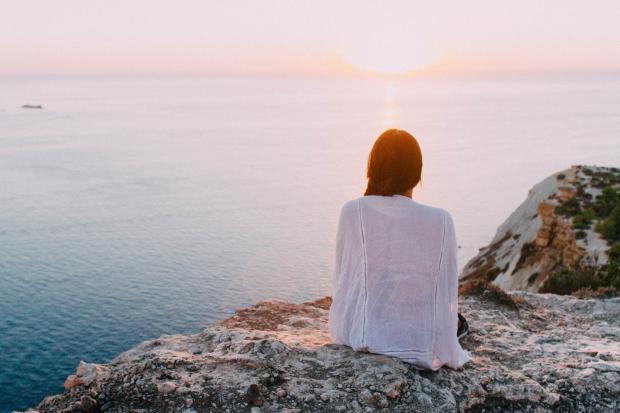 девушка на вершине горы встречает рассвет у моря