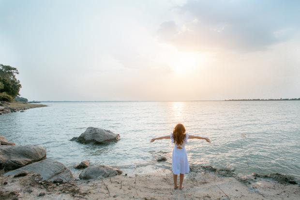 девушка в белом платье стоит на берегу моря