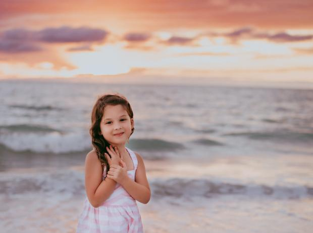 маленькая девочка в белом платье стоит на берегу моря