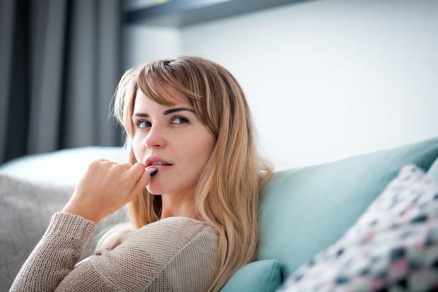 девушка в серой кофте сидит на диване и думает