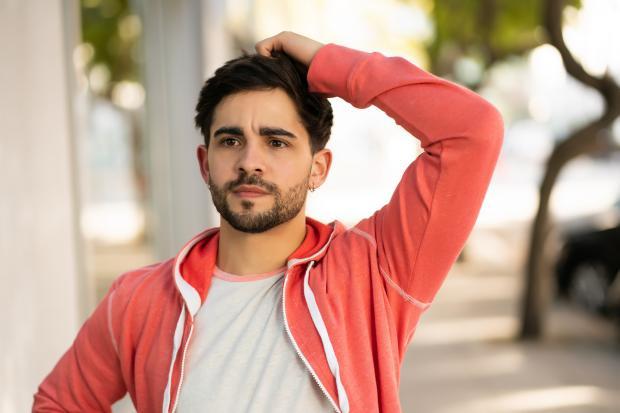 молодой человек в белой футболке и красной куртке на улице