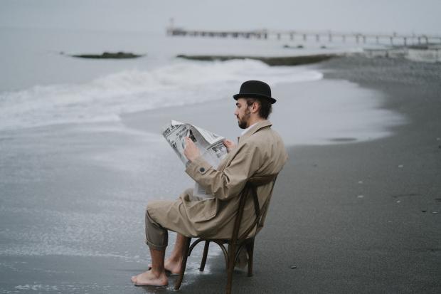 мужчина в плаще и шляпе с газетой в руках сидит на стуле на берегу