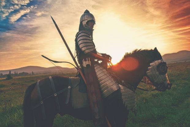 воин с копьем и в доспехах едет на коне