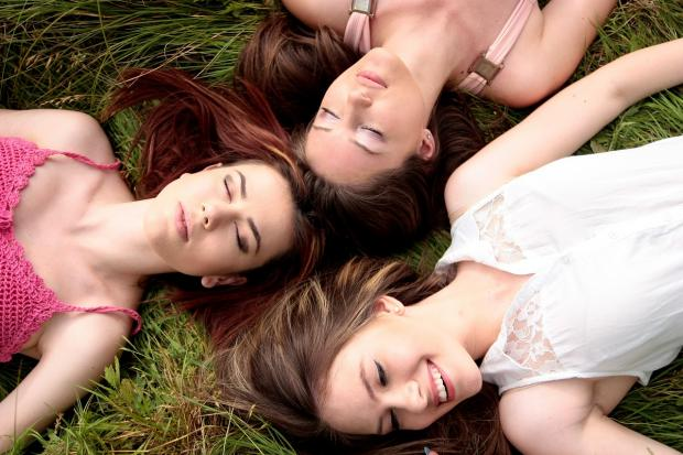 три подруги лежат на траве и смеются