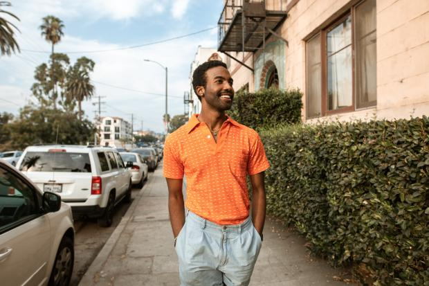 молодой человек в светлых брюках и оранжевой футболке
