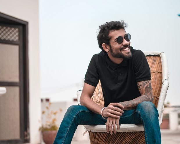 молодой мужчина в черной футболке и джинсах сидит на стуле