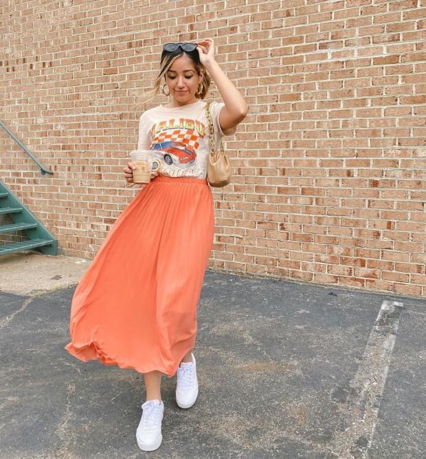 идет девушка в оранжевой юбке и белых кроссовках