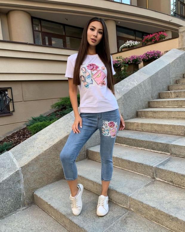 на лестнице стоит девушка в джинсах и футболке с аппликацией