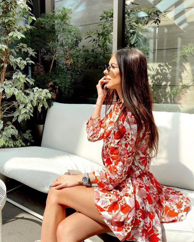 сидит брюнетка с распущенными волосами в платье с цветочным принтом