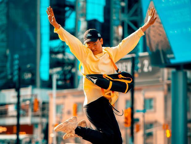 молодой мужчина в желтом худи прыгает в городе