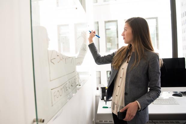 девушка в офисе что-то пишет на доске