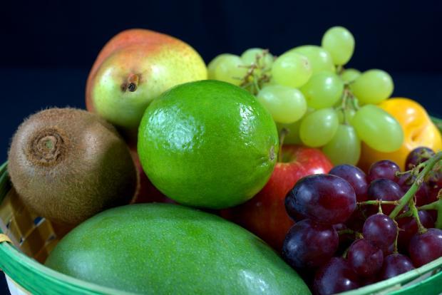 в зеленой вазе лежат фрукты