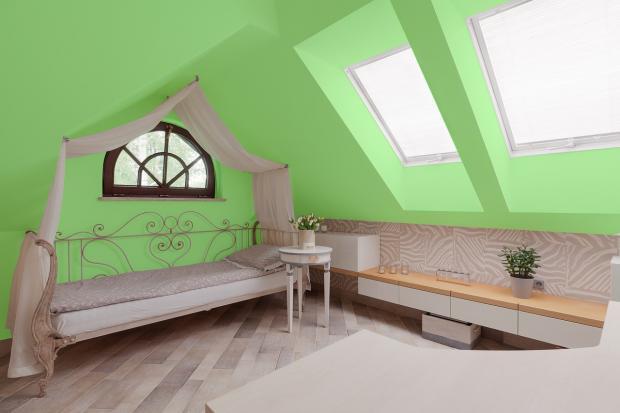 кровать стоит в спальне с зелеными стенами