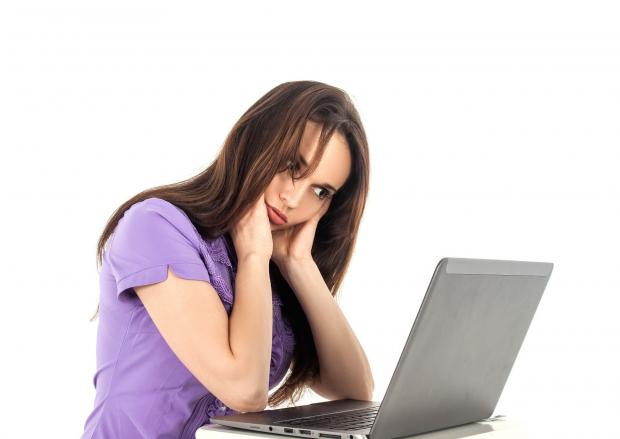 уставшая девушка сидит перед ноутбуком