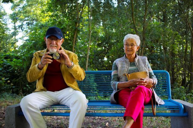 пожилые мужчина и женщина сидят на скамейке