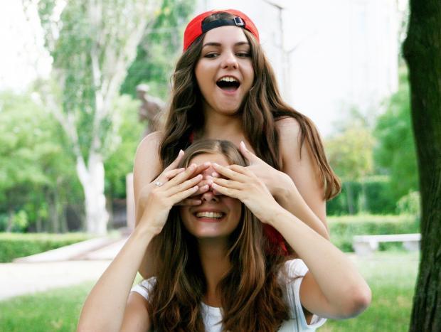 девушка в красной кепке закрыла глаза подруге