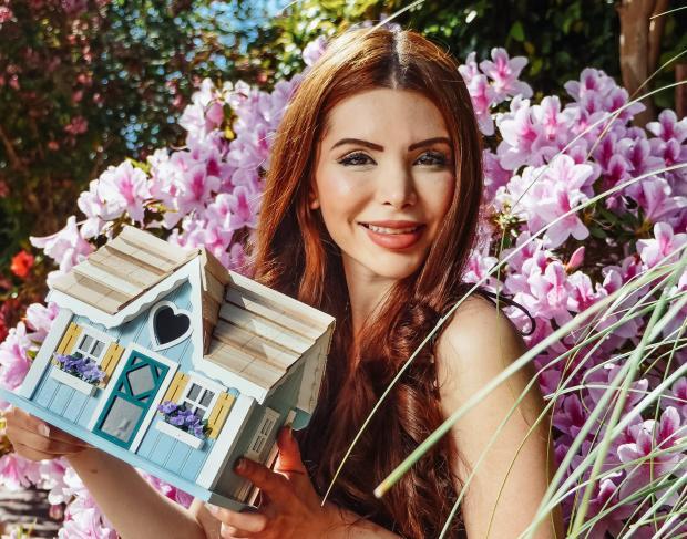 Девушка на фоне цветов с домиком в руках
