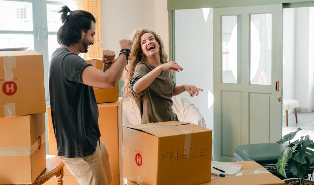 молодая пара смеется в квартире